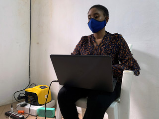 Gbemisola Olowokere, 23, works on her laptop powered by solar energy from Lumos in her home amid the spread of coronavirus disease (COVID-19) in Lagos