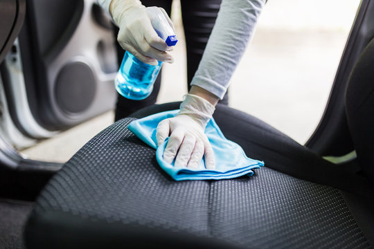Woman with protective gloves cleaning car seat with microfiber cloth and spray bottle disinfectant.