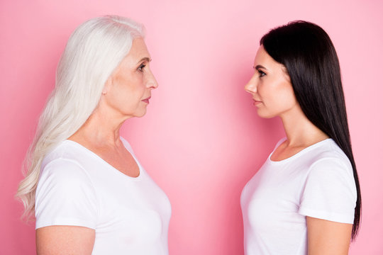 Profile photo of pretty old mother young daughter two ladies standing opposite look eyes see age difference wisdom wear casual white t-shirts isolated pastel pink color background