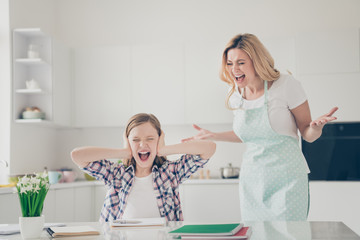 Photo of two people crazy furious mother shout her small daughter sit table cant write essay avoid close cover ears palms yell wear dotted apron in house kitchen indoors