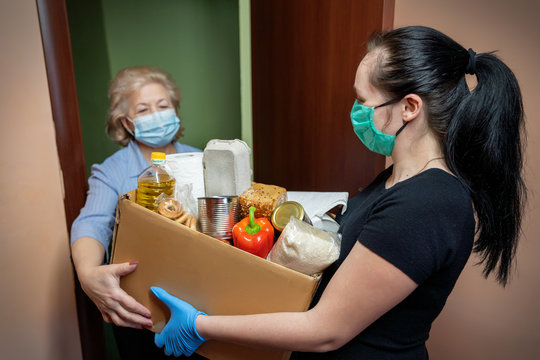 Volunteer young female in medical mask and gloves handing an senior woman a box with food. Donation, support people in quarantine, coronavirus