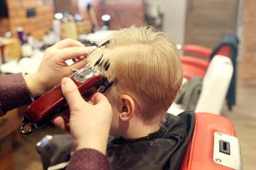 Hair cutting with a clipper. A child, a boy, during a haircut at a barbershop.