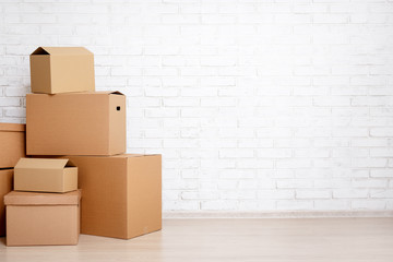 moving day concept - cardboard boxes and copy space over white brick wall