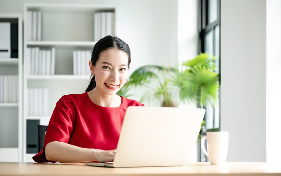 Work at home, Video conference, Online meeting video call, Portrait of beautiful young asian woman looking at computer screen watching webinar and working on laptop in workplace
