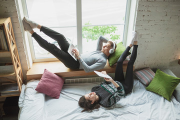 Using devices lying down in bedroom near window. Quarantine lockdown, stay home concept - young...
