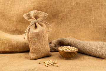 Fototapete - Soy beans in a sack and in a wooden bowl on sackcloth.