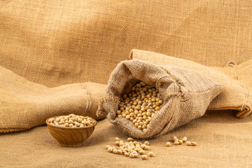 Fototapete - Closeup of soy beans in a sack and in a wooden bowl on sackcloth.