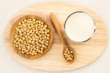 Fototapete - Top view of soybean milk in a glass with soy beans in wooden plate and in wooden spoon on wooden board.