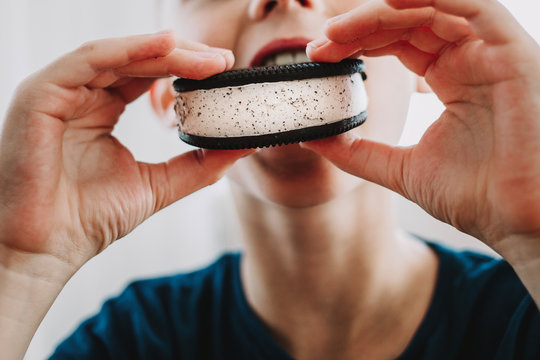 Close up of young boy eating ice cream sandwich.