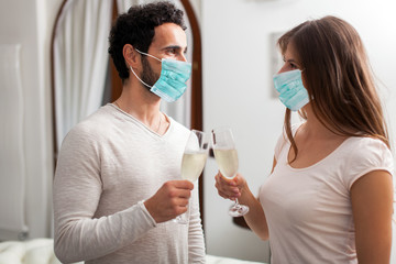 Man and Woman hands toasting with Champagne wearing masks, coronavirus concept