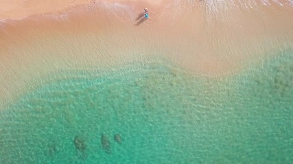 Wall Mural - Couple walks on the tropical beach on Oahu island in Hawaii. Top down view of the perfect sandy beach with breaking waves and couple walking along the shore