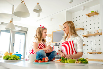 Mother and daughter having fun  together while preparing healthy meal with vegetables in the kitchen
