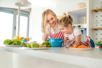 Cute little girl and her beautiful mother having fun while cooking together in kitchen at home