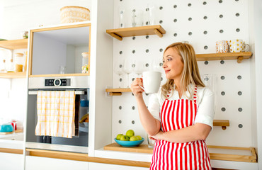 Young smiling cheerful woman drinking coffee in the kitchen