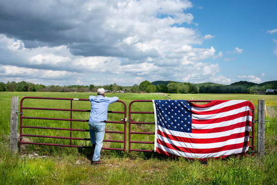 Farmer leaning on metal fence in grassy agricultural field, American flag draped over fence, blue sky white clouds