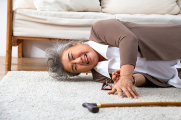 Asian senior woman falling down on carpet and lying on the floor in living room at home, Falls of older adults concept