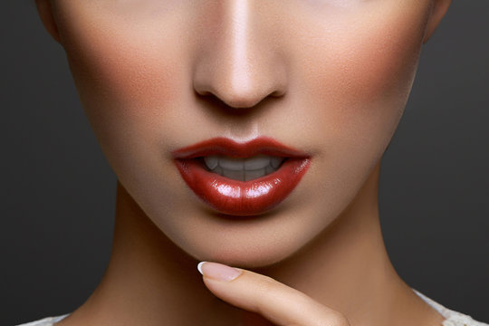 Close-up portrait of beautiful young woman lips with bright red lipstick