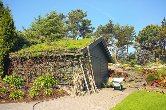 Typical garden shed with grass roof, in a beautiful garden with a wheelbarrow, Stavanger, Norway.