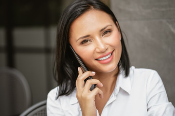 Happy young business woman talking on phone while sitting during rest in coffee shop. Attractive female with cute smile having talking on phone and looking at camera. Technology Communication Concept.