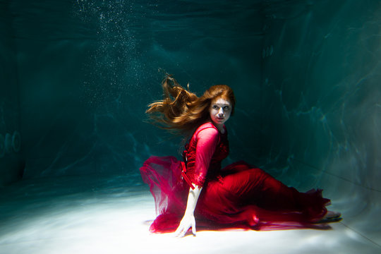 Beautiful girl underwater in a red dress swims in the pool. Tenderness and elegance. Bubbles and a lot of water