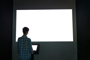 Woman looking at white blank large interactive wall display in dark room of technology exhibition - back view. Evening time, low light. Mock up, template, copyspace, education and technology concept