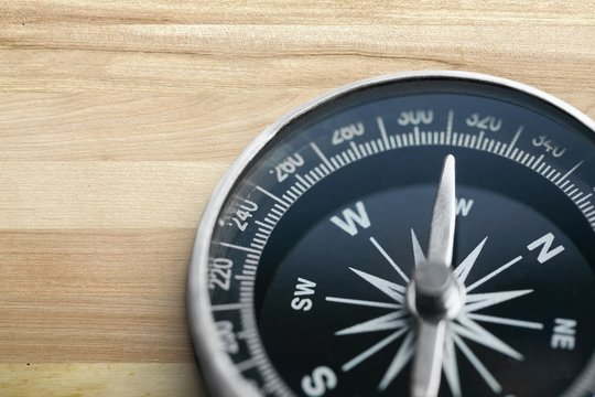Brass antique classical compass on wooden desk