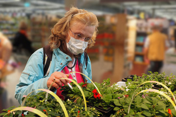 Woman with face mask in a supermarket looking at flowers Fototapete
