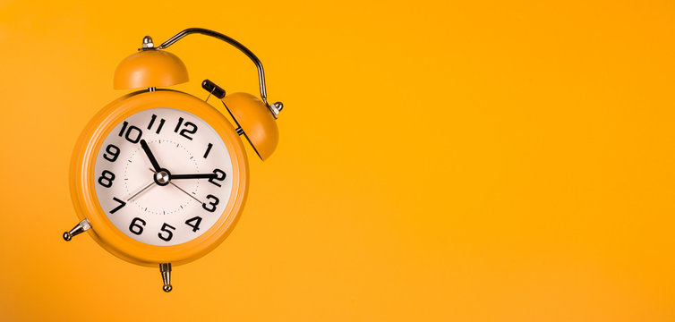 orange alarm clock on orange background