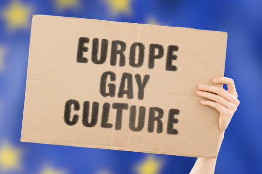 "The phrase "" Europe gay culture "" on a banner in men's hand with blurred European flag on the background. Human rights. Freedom. LGBT law in EU. Free. Gender. Sex. Justice for all"