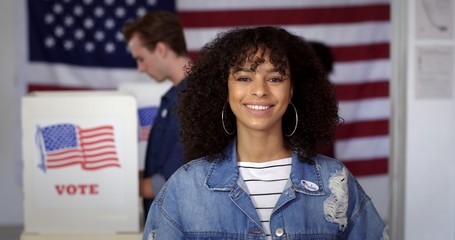 """MCU Young Hispanic woman in denim jacket with a new """"I Voted"""" sticker, smiling and standing in front of voters in polling booths with US flag in background"""