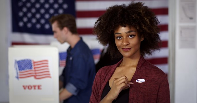 "MCU Young mixed race American woman displays ""I Voted"" sticker while standing proud in front of polling booths with other voters, US flag at rear"