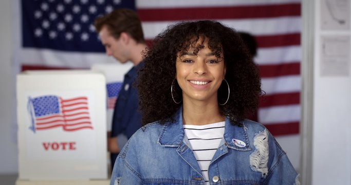 "MCU Young Hispanic woman in denim jacket with a new ""I Voted"" sticker, smiling and standing in front of voters in polling booths with US flag in background"
