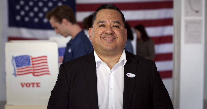 """MCU Hispanic man in white shirt and black jacket with """"I Voted"""" sticker, smiles while standing in front of other voters at polling booths with US flag in rear"""