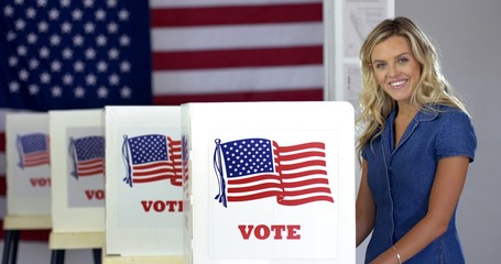 MS Young blonde woman casting vote at booths, looks up and smiles in polling station with US flag.
