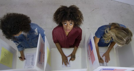 MS Overhead view three young women with mixed-race woman in center, looking up as she fills in ballot at voting booths in polling station.