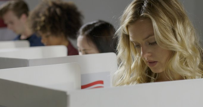 Young blonde woman considers her vote in booth with others at polling station.  US flag on wall in background.
