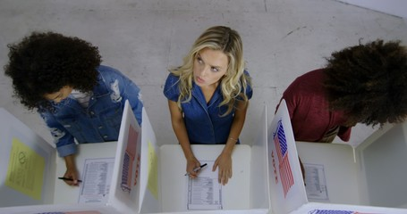 LS Wide overhead view three young women with blonde woman in center, looking up as she fills in ballots at voting booths in polling station