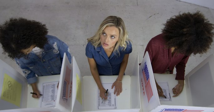 MS Overhead view three young women with blonde woman in center, looking up as she fills in ballot at voting booths in polling station