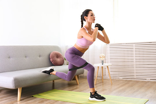 Stay at home workout concept. Young attractive woman performing bodyweight fitness exercises at her apartment. Beautiful female doing bulgarian split squats. Close up, copy space, background.