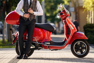 man in classic vest near a red vintage motorbike scooter.