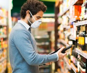 Man choosing a wine bottle during coronavirus pandemic