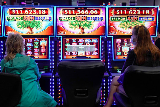 Casino patrons play at spaced out slot machines at the recently reopened Lucky Star Casino in El Reno