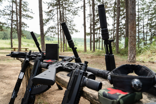 Laserwar or lasertag laser war tag equipment weapon on the wooden bench in the woods in sunny day guns rifles gun replica medic kit bomb and head band target sensor close up
