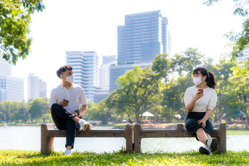 Two Asian young man and woman chatting in smartphone and wearing mask sitting distance of 6 feet...