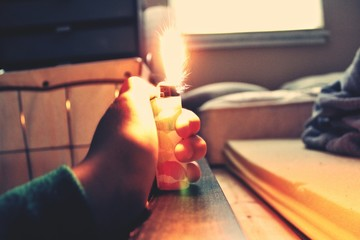 Cropped Hand Holding Illuminated Cigarette Lighter At Home