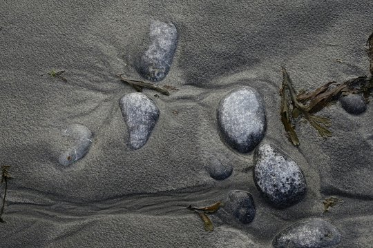 High Angle View Of Pebbles On Wet Sand