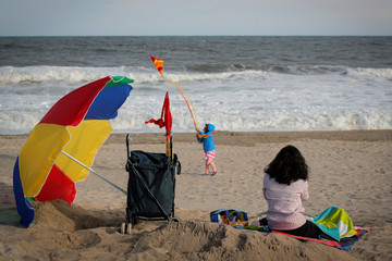A woman watches as a child plays on the beach, during the outbreak of the coronavirus disease (COVID-19), in the Rockaway section of Queens, New York