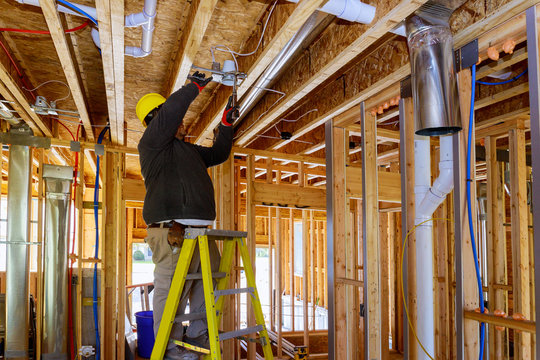 The electrician nailing to the ceiling lamp, installs the lighting lamp