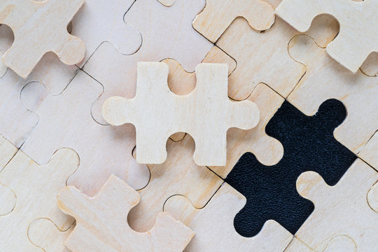 wooden jigsaw puzzle pieces on black background