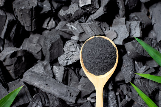 Black ground charcoal, crushed and placed in a spoon placed on a large pile of charcoal.
